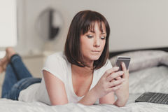 Beautiful woman writes sms on smartphone in white tshirt and blu Royalty Free Stock Images