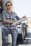 Beautiful woman writing on clipboard while standing by a flatbed truck Stock Photography