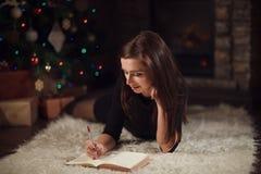 Beautiful woman writing list of wishes near christmas tree Royalty Free Stock Image