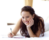 Beautiful woman writing notes in bed Royalty Free Stock Image