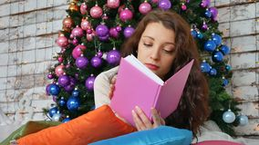 Beautiful woman with Xmas tree in background reading a book lying on bright pillows. Portrait of girl posing pretty stock video