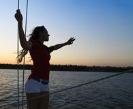 Beautiful woman on yacht deck in sunset light Stock Images