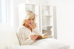 Beautiful woman yawning while reading a book Stock Photography