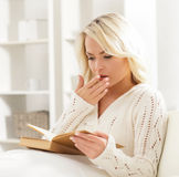 Beautiful woman yawning while reading a book Royalty Free Stock Photography