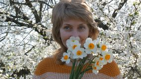 Beautiful woman in years holding a bouquet of daffodils looks at camera and smiles. A woman with beautiful, unusual. A beautiful woman in years holding a bouquet stock video