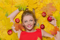 Beautiful woman in yellow autumn leaves and apples Royalty Free Stock Photography