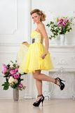 Beautiful woman in yellow dress in luxury studio. Royalty Free Stock Image
