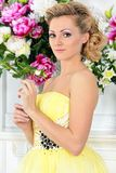 Beautiful woman in yellow dress in luxury studio. Stock Photo