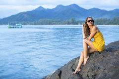 Beautiful woman in a yellow dress, sits on a cliff overlooking the Sea in the evening time. Stock Images