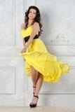 Beautiful woman in yellow evening dress. Stock Photos