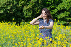 Beautiful woman in a yellow flowers field Stock Image