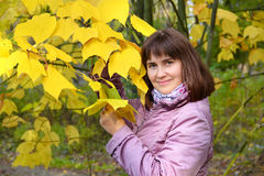 Beautiful woman in yellow foliage Royalty Free Stock Photo
