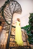 A beautiful woman in a yellow long dress is standing on a spiral staircase back. A girl dreams in a decorated living room for Chri. Stmas or New Year royalty free stock images