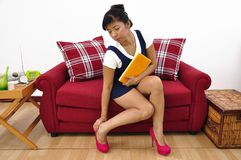 Asianl woman sits on red sofa and holds yellow not Royalty Free Stock Image