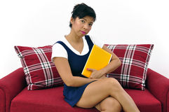 Beautiful woman with yellow notebook on red sofa Royalty Free Stock Photo
