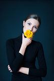 Beautiful woman with yellow rose flower in her mouth Royalty Free Stock Photo