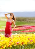 Beautiful woman in yellow tulips Stock Image