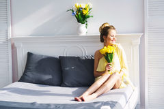 Beautiful woman with yellow tulips Stock Photography