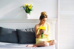 Beautiful woman with yellow tulips Stock Photo