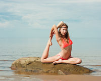 Beautiful woman yoga on the beach. Sits in the swan position royalty free stock photos