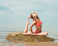Beautiful woman yoga on the beach. Sits in the swan position royalty free stock photo