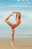 Beautiful woman yoga on the beach. Sitting in the Dancing Shiva position stock photography
