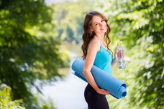 Beautiful woman with a yoga mat outdoors. Royalty Free Stock Photos