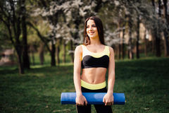 Beautiful woman with a yoga mat outdoors in park royalty free stock image