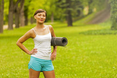 Beautiful woman with a yoga mat outdoors. Stock Photo