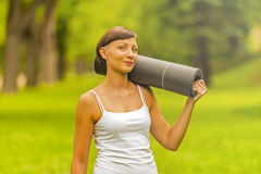 Beautiful woman with a yoga mat outdoors. Stock Image