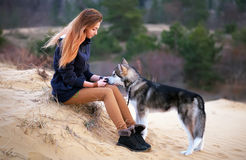 Beautiful woman with young dog Malamute on the sand. Royalty Free Stock Photo