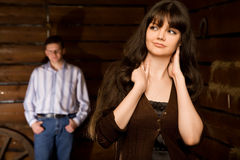 Beautiful woman and young man in wooden log hut Stock Photography