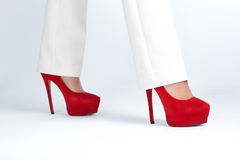 Beautiful womanish feet are in red shoes Stock Images