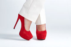 Beautiful womanish feet in red shoes standing on light background. Stock Photo
