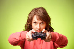 Beautiful womanl with gamepad playing vieogame. Over green background. Focus on face Royalty Free Stock Photos