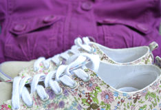 Beautiful womanly shoes with flowers and purple jacket on the background. Royalty Free Stock Image