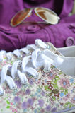 Beautiful womanly shoes with flowers, purple jacket and sunglasses on the background. Royalty Free Stock Photo