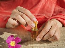 Beautiful womans hands holding a small vial of scented oil. Arab Attar. Stock Images