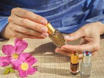 Beautiful womans hands holding a small vial of scented oil. Arab Attar. Royalty Free Stock Photos