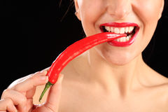 Beautiful womans mouth biting on red chili pepper Royalty Free Stock Photos