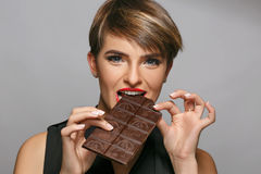 Beautiful womanwith blue eyes and red lips enjoys eating tasty milk chocolate at a photo studio. Royalty Free Stock Image