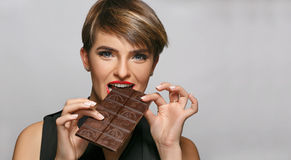 Beautiful womanwith blue eyes and red lips enjoys eating tasty milk chocolate at a photo studio. Stock Photos