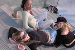 Beautiful Women. Three friends hanging out in a shopping mall area. Three fashion models sitting on some steps outside Stock Image