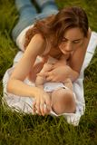 Beautiful woman with adorable baby lying on the green grass. Hap stock photos