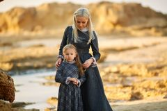 Mother and daughter standing on coast stock photos