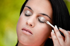 Beautiful women applying eye shadow Royalty Free Stock Photo