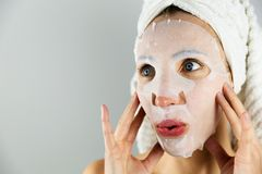 Beautiful women applying facial mask with moisturizer. Beautiful woman applying facial mask with moisturizer in a natural light royalty free stock images