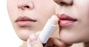 Beautiful woman applying hygienic lip balm. Beautiful women applying hygienic lip balm. Lipcare Stick. Lips Skin Care Concept Royalty Free Stock Photo
