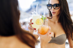 Beautiful women on beach enjoying cocktails Royalty Free Stock Image