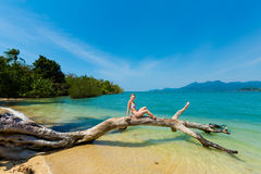 Beautiful women on beach. Summer landscape with beautiful caucasian girl sitting on fallen tree on remote tropical island near koh Chang in Thailand. Seascape Royalty Free Stock Images